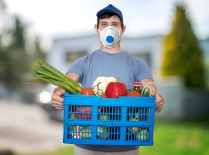 Man with FFP3 respirator face mask is delivering food and groceries during virus epidemic.